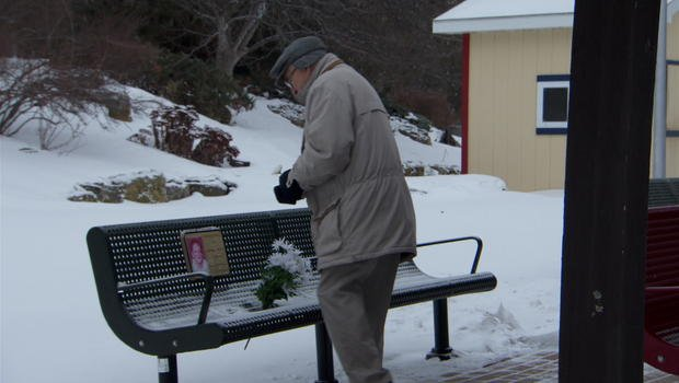Bud Caldwell leaves daisies for his wife at her memorial bench (CBS NEWS)