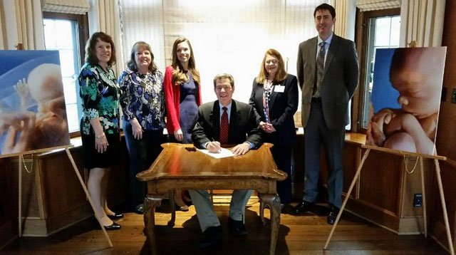 Republican Gov. Sam Brownback signed the measure Tuesday in a private ceremony at the governor's residence. A photo posted by his office on Twitter shows him flanked by anti-abortion leaders and large photos of fetuses.