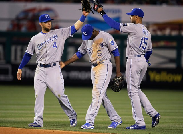 Kansas City Royals' Alex Gordon, Lorenzo Cain and Alex Rios celebrate their team's 6-4 win against the Los Angeles Angels in a baseball game, Saturday, April 11, 2015, in Anaheim, Calif. (AP Photo/Jae C. Hong)