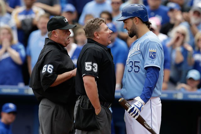 Umpires Greg Gibson (53) and Jim Joyce (66) talk with Kansas City Royals' Eric Hosmer (35) during a baseball game against the Oakland Athletics at Kauffman Stadium in Kansas City, Mo., Sunday, April 19, 2015. (AP Photo/Orlin Wagner)