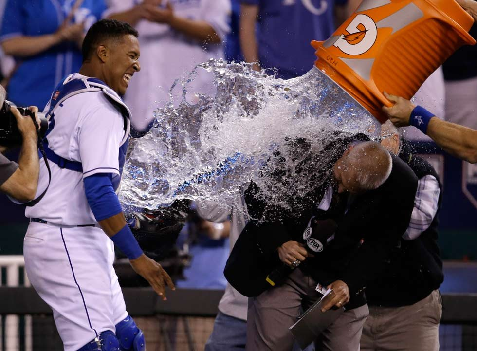 Royals catcher Salvador Perez dodges the water cooler as it lands on Fox announcer Joel Goldberg following a baseball game against the Detroit Tigers at Kauffman Stadium Friday, May 1. The Royals defeated the Tigers 4-1. (AP Photo/Orlin Wagner)