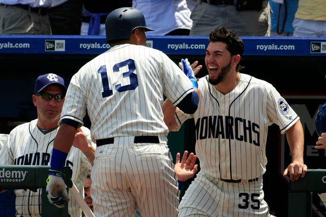 Wearing the uniform of the former Negro League's Kansas City Monarchs, Kansas City Royals' Salvador Perez (13) is congratulated by Eric Hosmer (35) after hitting a solo home run in the second inning. (AP Photo/Colin E. Braley)