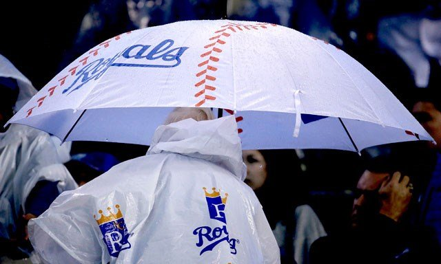 A fan heads for shelter after a rain delay was called during the sixth inning of a baseball game between the Kansas City Royals and the St. Louis Cardinals, Saturday, May 23, 2015, in Kansas City, Mo. (AP Photo/Charlie Riedel)