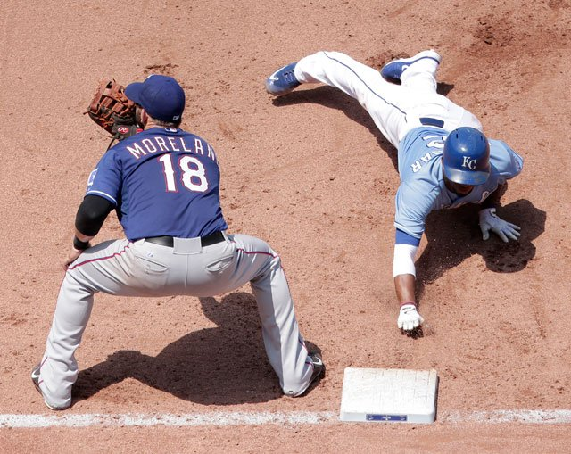 Kansas City Royals' Alcides Escobar, right, beats the tag by Texas Rangers first baseman Mitch Moreland (18) during a pickoff-attempt during the fifth inning of a baseball game Sunday, June 7, 2015, in Kansas City, Mo. (AP Photo/Charlie Riedel)