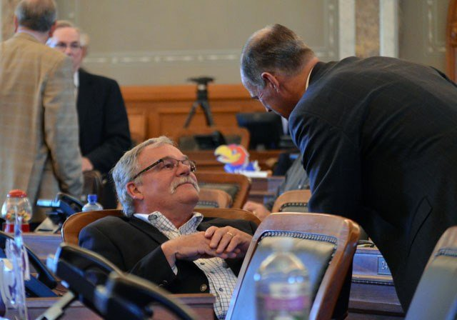 Kansas state Rep. John Barker, left, R-Abilene, confers with Rep. Steve Johnson, right, R-Assaria, during the House's session, Tuesday, June 9, 2015, at the Statehouse in Topeka, Kan. (AP Photo/Nicholas Clayton)