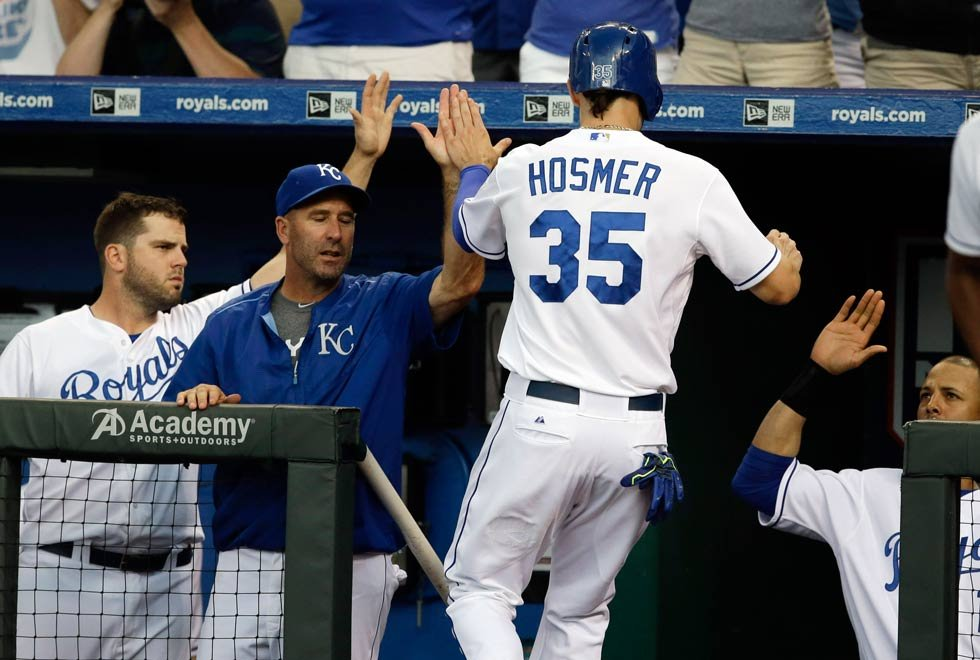 Kansas City Royals' Eric Hosmer (35) is greeted at the dugout after scoring a run during the first inning of a baseball game against the Milwaukee Brewers at Kauffman Stadium in Kansas City, Mo., Thursday, June 18, 2015. (AP Photo/Orlin Wagner)