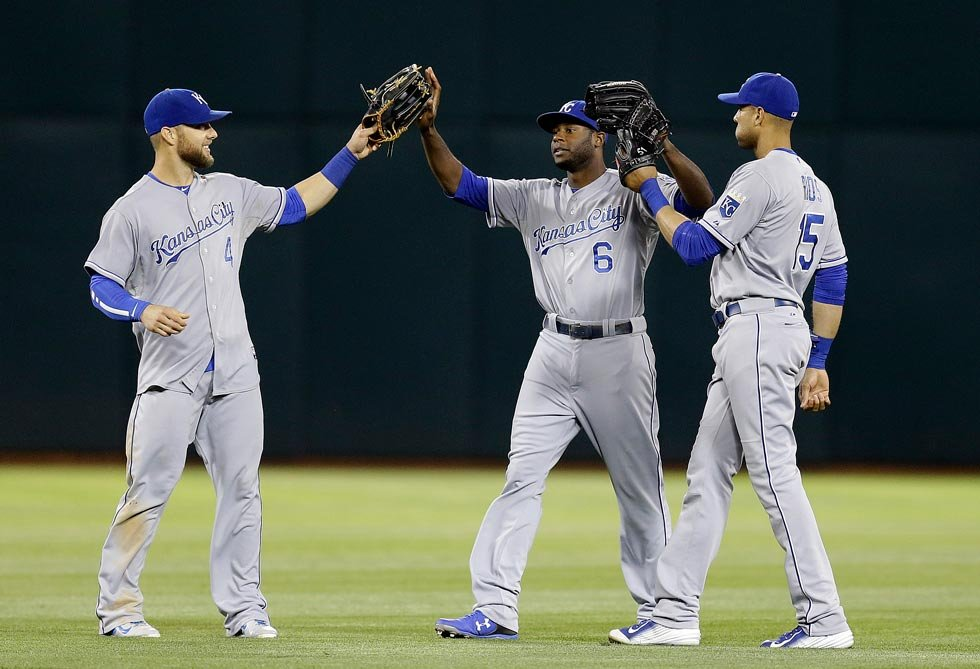 From left, Kansas City Royals' Alex Gordon, Lorenzo Cain, and Alex Rios celebrate a 5-2 defeat of the Oakland Athletics in a baseball game Friday, June 26, 2015, in Oakland, Calif. (AP Photo/Ben Margot)