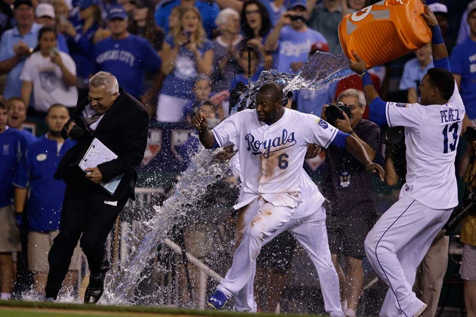 Royals' Lorenzo Cain, left, tries to dodge a cooler of water being emptied by teammate Salvador Perez (13) following a baseball game against the Minnesota Twins at Kauffman Stadium Friday, July 3. Cain scored the winning run. (AP Photo/Orlin Wagner)