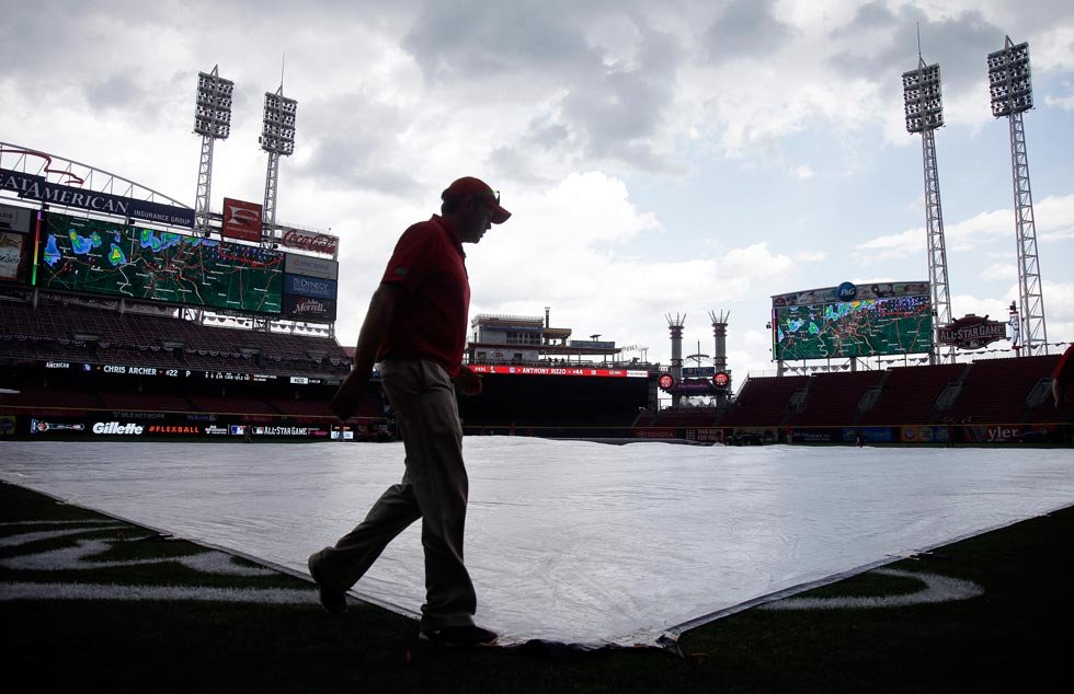 A grounds crew member helps to put the tarp on the field before the start of batting practice before the start of the MLB All-Star baseball game, Tuesday, July 14, 2015, in Cincinnati. (AP Photo/John Minchillo)