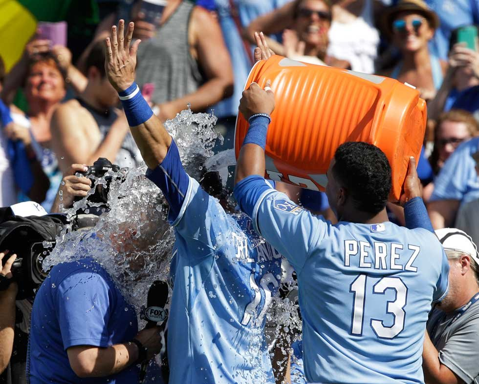 Royals broadcaster Joel Golberg and outfielder Paulo Orlando are drenched in water by Salvy Perez after Sunday's win (AP)