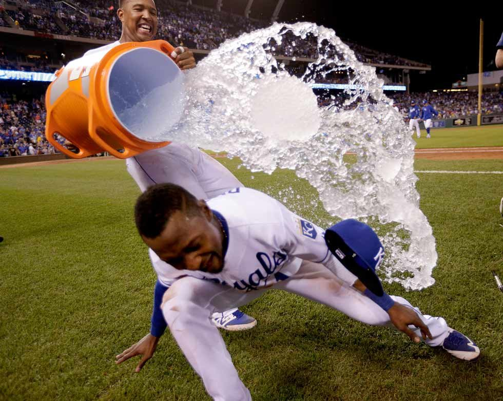 Kansas City Royals' Salvador Perez, back, douses Jarrod Dyson after a baseball game against the Pittsburgh Pirates on Tuesday, July 21, 2015, in Kansas City, Mo. The Royals won 3-1. (AP Photo/Charlie Riedel)