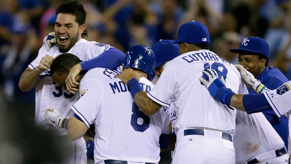 Kansas City Royals' Eric Hosmer, left, mobs teammate Alcides Escobar with Mike Moustakas (8) and Cheslor Cuthbert (19) following his game-winning hit during the tenth inning of a baseball game against the Houston Astros (AP)