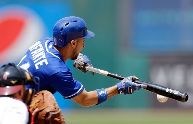 Kansas City Royals' Omar Infante bunts for a single against Cleveland Indians starting pitcher Corey Kluber in the fifth inning of a baseball game, Wednesday, July 29, 2015, in Cleveland. (AP Photo/Tony Dejak)