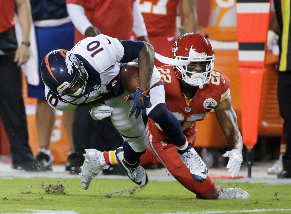 Denver Broncos wide receiver Emmanuel Sanders (10) is tackled by Kansas City Chiefs defensive back Marcus Peters (22) during the first half of an NFL football game in Kansas City, Mo., Thursday, Sept. 17, 2015. (AP Photo/Charlie Riedel)