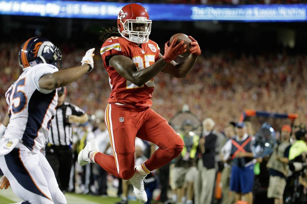 Kansas City Chiefs running back Jamaal Charles (25) scores a touchdown against Denver Broncos cornerback Chris Harris Jr., left, during the first half of an NFL football game in Kansas City, Mo., Thursday, Sept. 17, 2015. (AP Photo/Charlie Riedel)