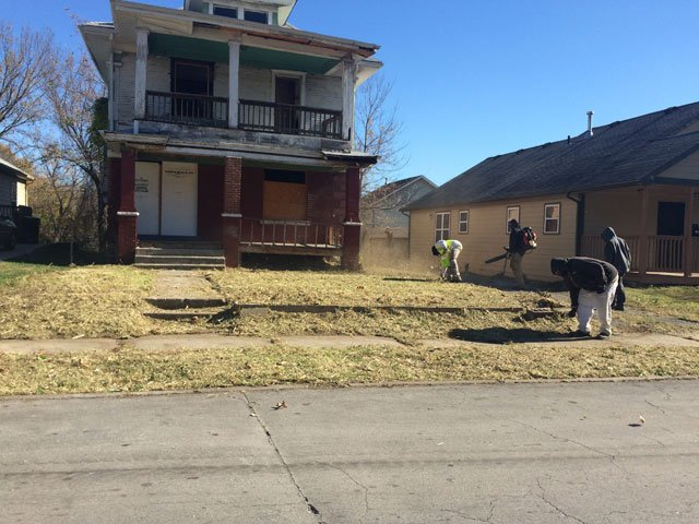 Workers were seen picking up trash and clearing out weeds outside the home. (Emily Rittman/KCTV5 News)
